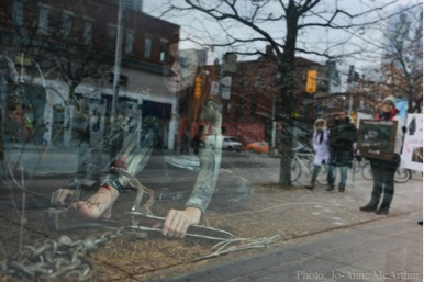 Shannon Kornelsen of Fur-Bearer Defenders in a leg-hold trap with scenes from Queen Street (including a couple wearing fur-trimmed jackets) reflected in the shop window.  Photo: JMcArthur/WeAnimals
